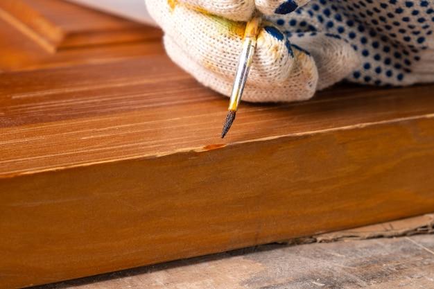 Restauration d'un gros plan de porte en bois, réparation de rayures sur une surface en bois.