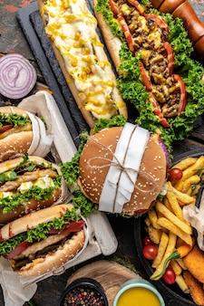Restauration rapide américaine. hamburgers, frites, hot-dogs. concept de restauration rapide et de mauvaise alimentation. vue de dessus