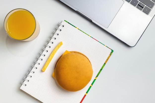 Restauration rapide au travail en train de grignoter. ordinateur portable, cahier, hamburger et frites au lieu de travail.