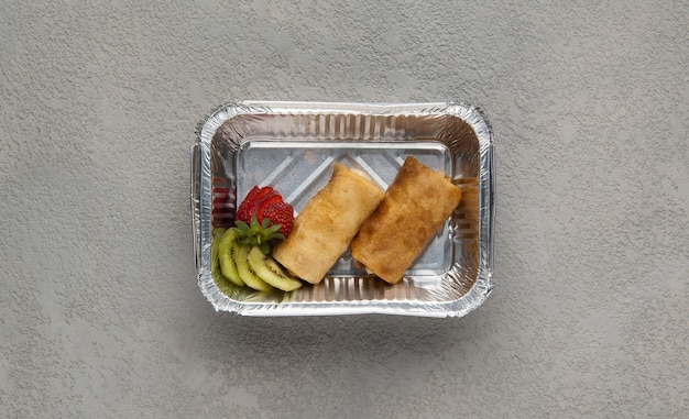 Restauration rapide dans une boîte en aluminium sur fond gris. une alimentation saine en gros plan