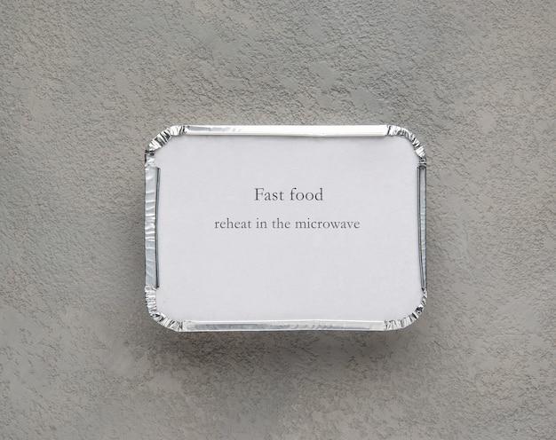 Restauration rapide dans une boîte en aluminium sur fond gris rugueux. nourriture pour homme d'affaires et personnes occupées