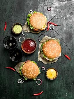 Restauration rapide hamburgers frais avec cola sur un fond rustique