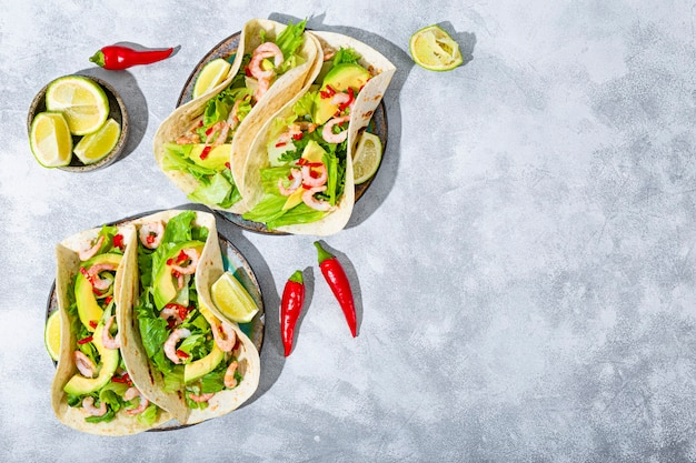 Restauration rapide mexicaine traditionnelle tacos mexicains aux crevettes et à l'avocat avec vue de dessus de piments verts et épices