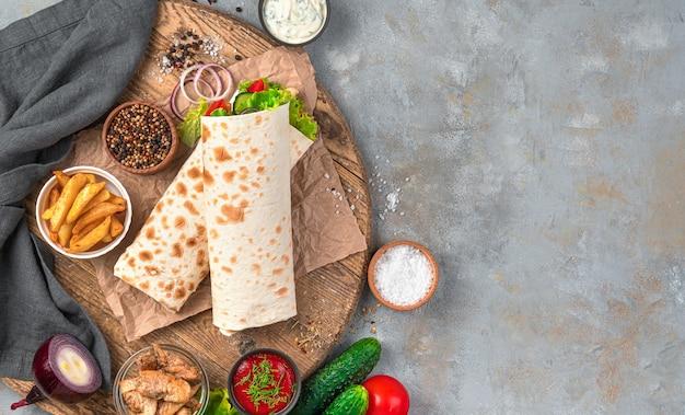 Restauration rapide : shawarma, burrito sur un mur gris avec des ingrédients. vue de dessus, copiez l'espace.