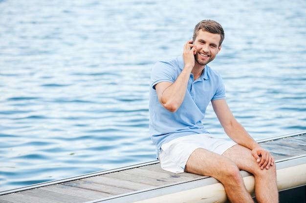 Rester connecté partout. beau jeune homme en polo parlant au téléphone portable et souriant alors qu'il était assis sur le quai