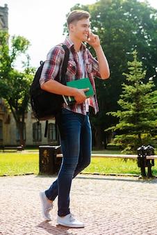 Rester en contact avec des amis. toute la longueur du bel étudiant masculin parlant au téléphone portable et souriant tout en marchant à l'extérieur