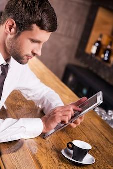 Rester en contact. vue de dessus d'un jeune homme confiant en chemise et cravate assis au comptoir du bar et travaillant sur une tablette numérique
