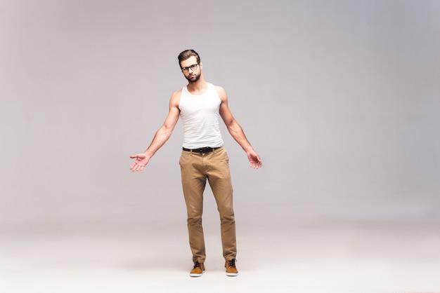 Rester décontracté. prise de vue en studio sur toute la longueur d'un beau jeune homme en tenue décontractée regardant la caméra et tendant les mains