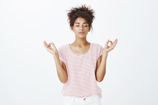 Rester femme calme et détendue avec une coiffure afro posant dans le studio