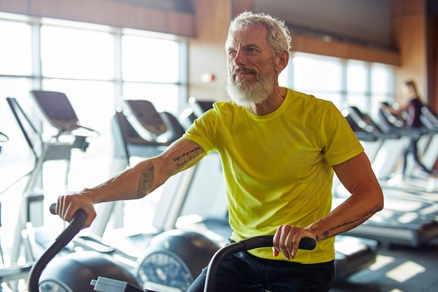 Rester en forme concentré homme athlétique mature en vêtements de sport faisant du vélo sur des vélos d'exercice à la salle de sport