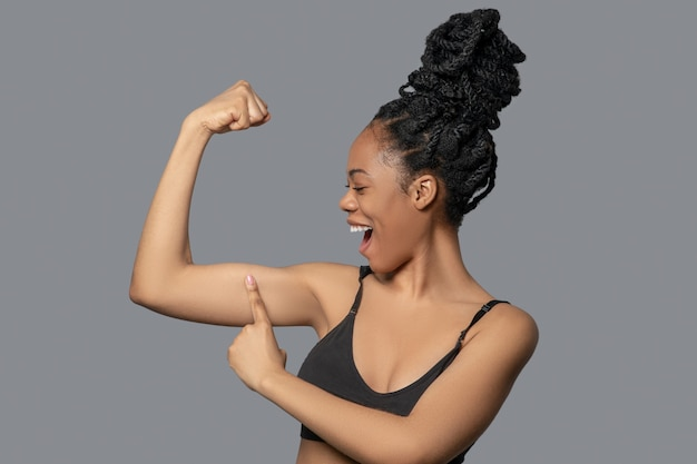 Rester en forme. mignonne mulâtre en noir montrant ses muscles