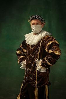 Rester à la maison. jeune homme en chevalier médiéval sur fond sombre portant un masque de protection contre le coronavirus. style rétro, concept de comparaison des époques. soins de santé, prévention de la propagation de la pandémie. être prudent.