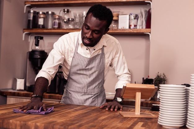 Rester propre. homme afro-américain positif à l'aide d'un plumeau tout en faisant le nettoyage