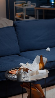 Restes de bouteilles de bière vides de pizza et serviettes sur table dans un salon en désordre