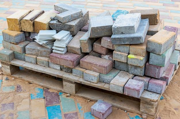 Restes de dalles de pavage en béton multicolores sur une palette après la pose de la passerelle.