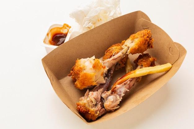 Les restes de pilons de poulet dans une boîte haute vue