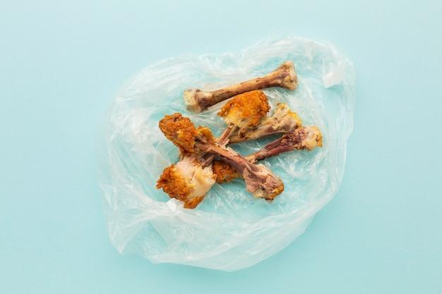 Restes de pilons de poulet dans un sac en plastique