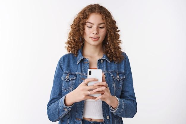 Restez encore un coup de plus. les taches de rousseur de fille rousse hipster mignonne focalisée tenant le smartphone regardent attentivement l'affichage du téléphone prenant une photo d'ami capturant l'image pour le blog internet, debout sur fond blanc