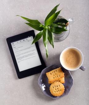 Restez à la maison biscuits, café et livre électronique sur la table - appréciez le concept de rester à la maison