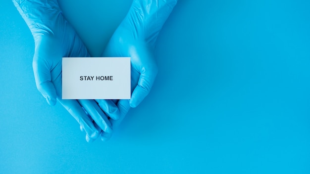 Restez à la maison et en bonne santé pour empêcher la campagne de propagation de covid-19, texte sur papier avec des gants bleus docteur
