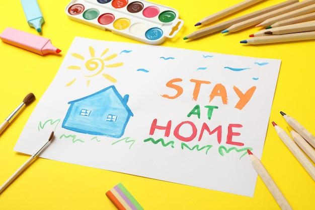 Restez à la maison concept sur une surface jaune. lieu de dessin pour enfants