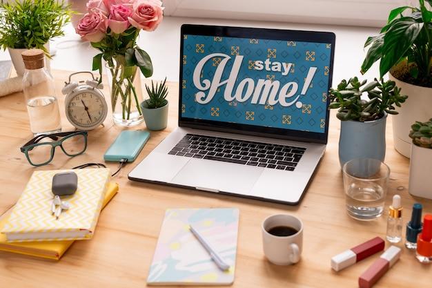 Restez à la maison sur écran d'ordinateur portable entouré de fleurs, réveil, livres, produits de maquillage, boissons et lunettes sur table