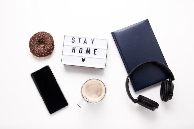 Restez à la maison, inscription de boxe. travail à distance en ligne à domicile. tablette casque et agenda sur un mur blanc.
