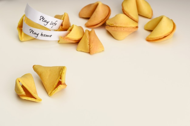 Restez à la maison, restez en sécurité dans les biscuits de fortune. pile de cookies fortune sur fond blanc avec espace de copie. cookie ouvert.
