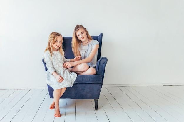 Restez à la maison restez en sécurité. deux enfants heureux assis sur une chaise bleue confortable relaxant jouant dans le salon blanc à l'intérieur. petite fille jouant avec une adolescente montrant ses soins amoureux. sœurs s'amusant à la maison.