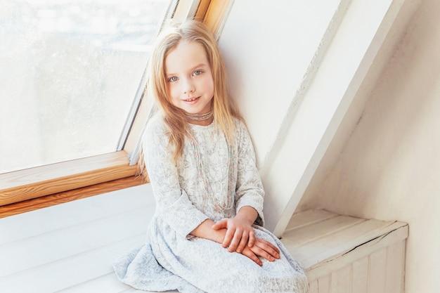 Restez à la maison restez en sécurité. petite jolie fille souriante douce en robe blanche assise sur le rebord de la fenêtre dans un salon lumineux à la maison à l'intérieur. jeunes écoliers de l'enfance se détendre concept.