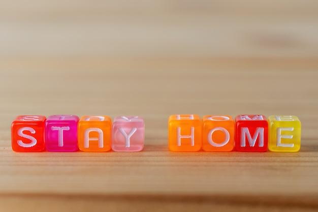 Restez à la maison texte avec des cubes de lettres de couleur sur fond de bois.