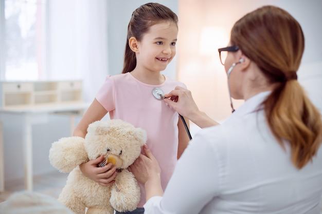 Restez une minute. happy jolly girl holding ours en peluche et rester tandis que femme médecin touchant le stéthoscope