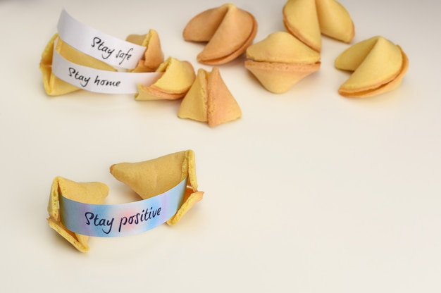 Restez souhait positif dans le cookie de fortune chinois ouvert. restez à la maison, restez en sécurité sur fond. fond blanc avec des biscuits de fortune et copie espace.