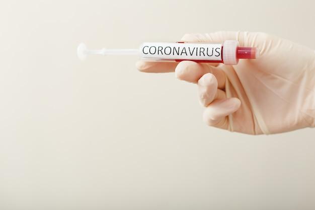 Résultat du test sanguin du coronavirus, sang infecté par le coronavirus dans un tube à essai sous vide dans la main du médecin, texte coronavirus.