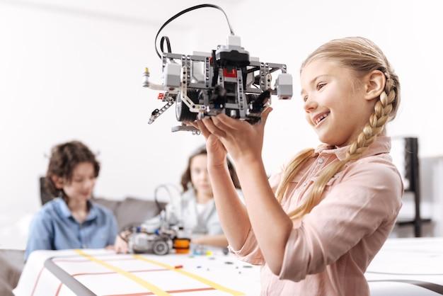Résultat réussi de mes efforts. fille déterminée et ludique travailleuse debout à l'école et tenant un robot électronique pendant que ses collègues travaillent sur le projet