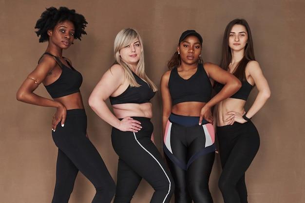 Résultats de l'entraînement. groupe de femmes multiethniques debout contre l'espace brun