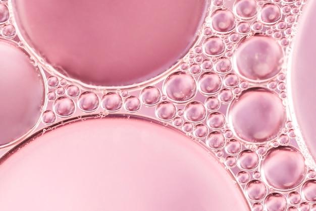 Résumé des bulles d'air dans un liquide sur fond flou rose