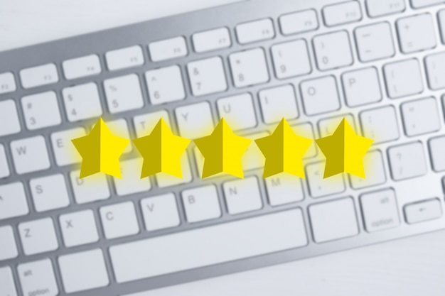 Résumé cinq étoiles sur un clavier flou montrant la meilleure note. excellente note. meilleur score. mise à plat.