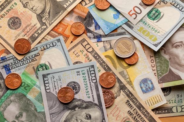 Résumé coloré composé de différentes pièces de métal, de billets américains, ukrainiens et de billets en euros. argent et finances, concept d'investissement réussi.