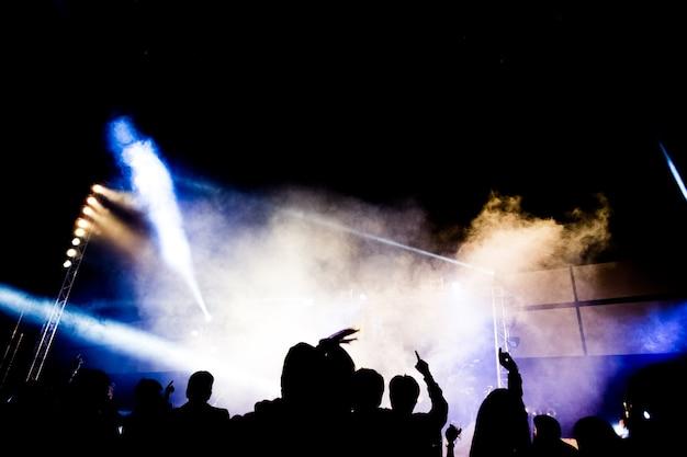 Résumé concert party silhoue avec la lumière et la fumée dans un moment heureux