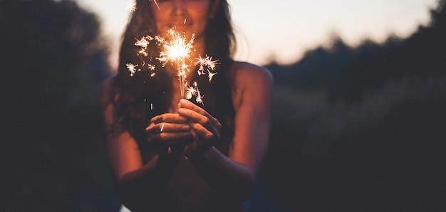 Résumé des flambeaux des feux de bengale pour la célébration, mouvement par le vent floue main de femme tenant brûlant de noël scintillent sur la nature et le ciel crépus
