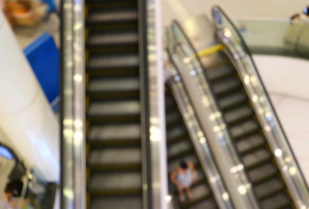 Résumé flou des escalators avec des gens qui descendent dans un centre commercial