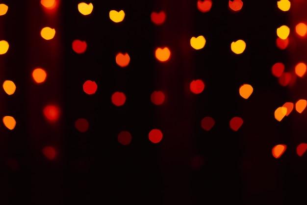 Résumé flou fond défocalisé noir, lumières rouges-orange-jaunes met en évidence, coeurs bokeh, flou
