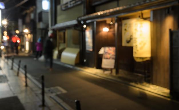 Résumé flou magasin en bois et restaurant avec lanterne allumée la nuit à kyoto, japon
