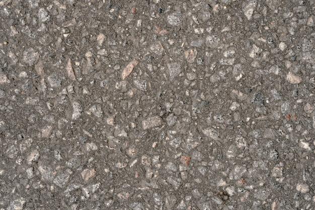 Résumé fond d'asphalte noir avec des inclusions de cailloux