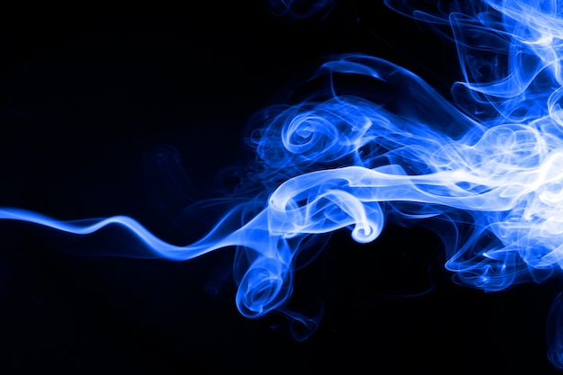 Résumé de fumée bleue sur fond noir. concept d'obscurité