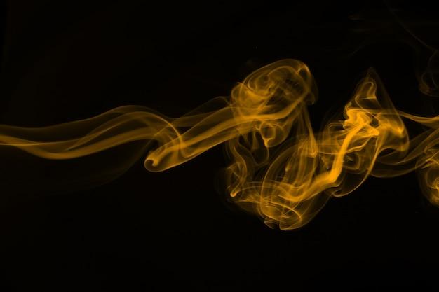 Résumé de fumée jaune sur fond noir