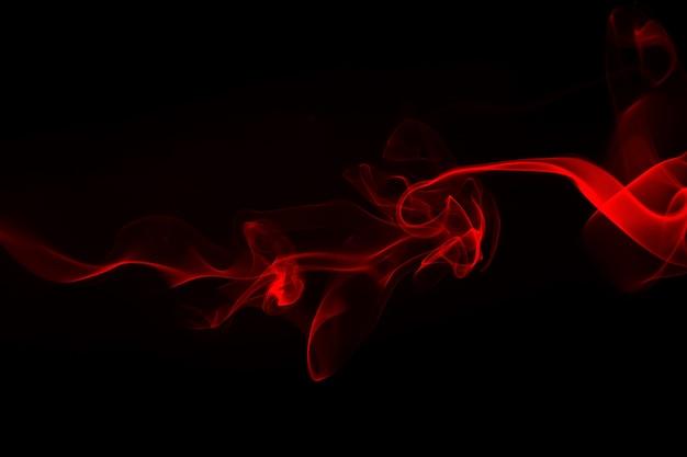Résumé de fumée rouge sur fond noir. conception du feu