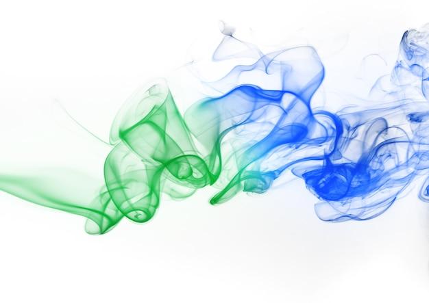 Résumé de fumée verte et bleue sur fond blanc