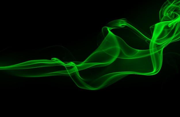 Résumé de fumée verte sur le concept de fond noir et l'obscurité